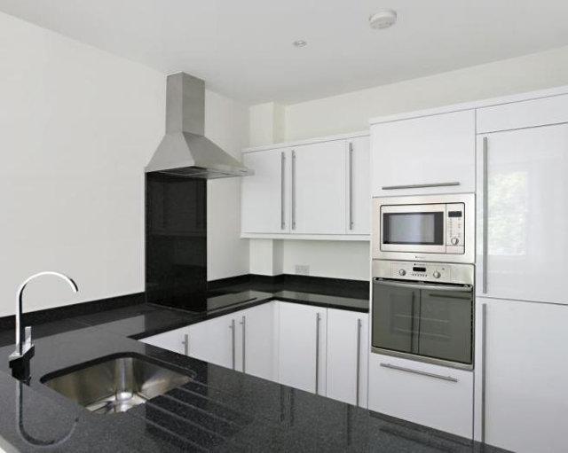 Белая П-образная кухня с черной столешницей