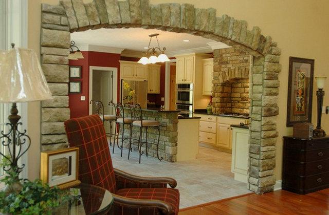 Большая арка между кухней и гостиной облицованная камнем