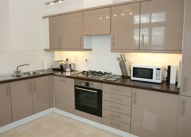 Современная угловая кухня с пластиковыми фасадами в интерьере